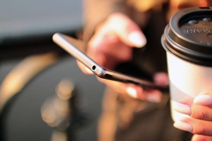 kobieta-korzystajaca-z-telefonu-pijaca-jednoczesnie-kawe-na-wynos